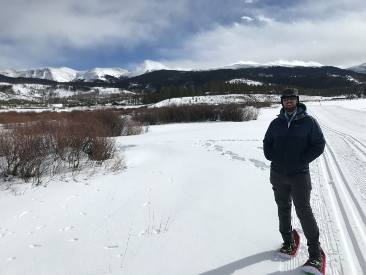 snowshoeing tips for etiquette: man with snowshoes standing on side of trail