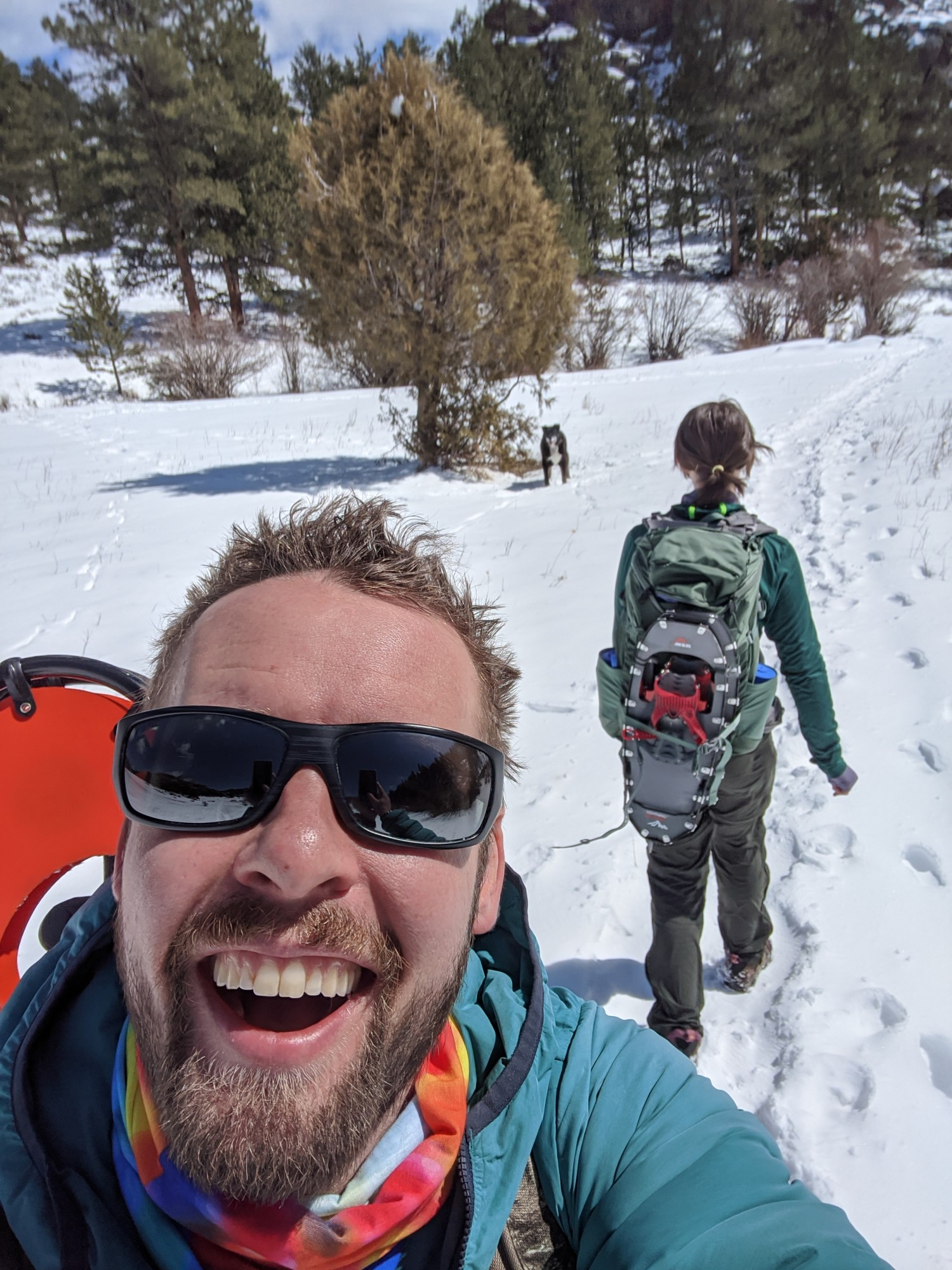 snowshoeing selfie with dog and woman walking away