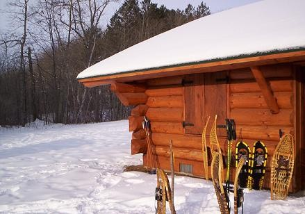 cabin in winter with snowshoes outside