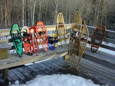 modern and traditional snowshoes on snow covered deck