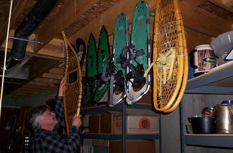 storing snowshoes: man hanging snowshoes in the garage