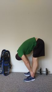 demo of standing forward bend: stretches for snowshoeing