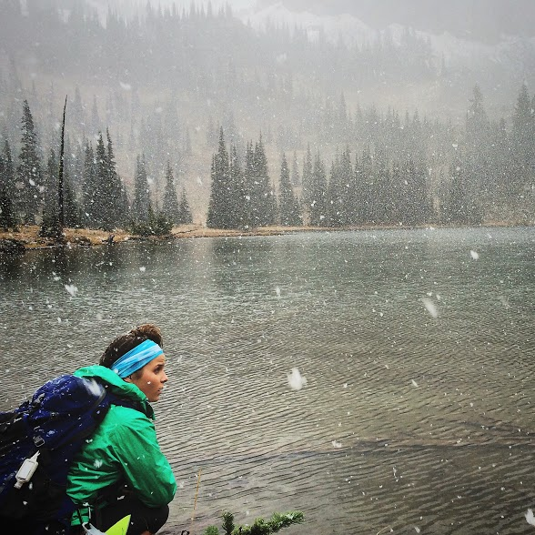 woman taking a break from trail running to watch the snow