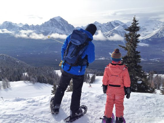 dad and son looking out in distance while snowshoeing