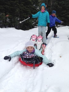 kids sledding down after snowshoeing
