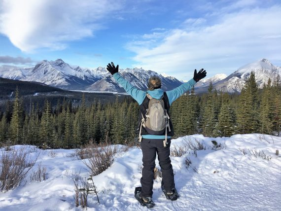 woman with hands raised looking at view while snowshoeing