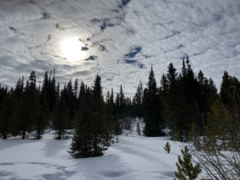 snowy landscape with cloud above and sun shining through