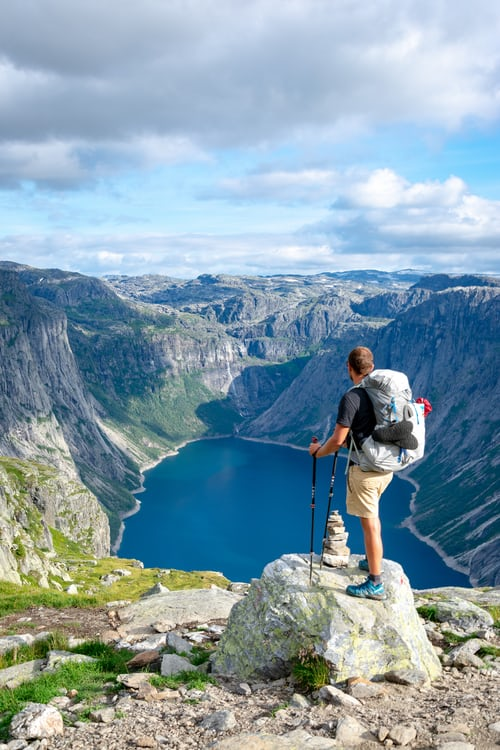 adapt to challenge: man overlooking a lake surrounded by mountains