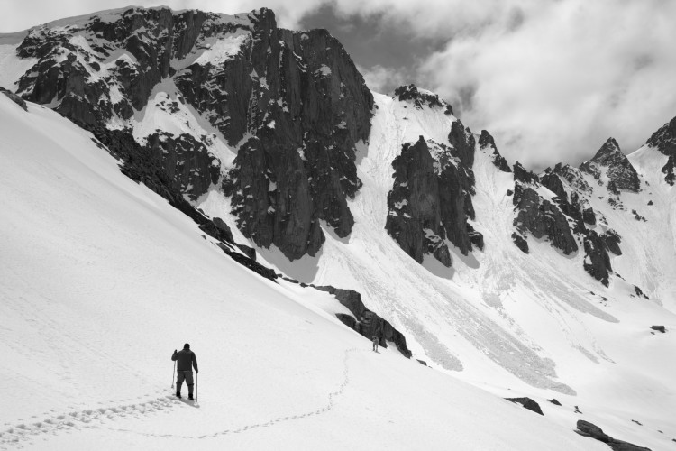 snowshoeing tips for safety: man snowshoeing near avalanche terrain