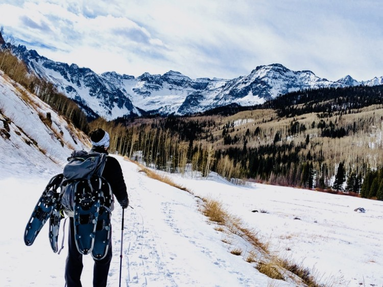 person with multiple pairs of snowshoes on their pack hiking through the mountains