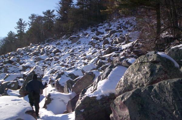 Hiking past quartzite talus on the Tumble Rocks Trail.