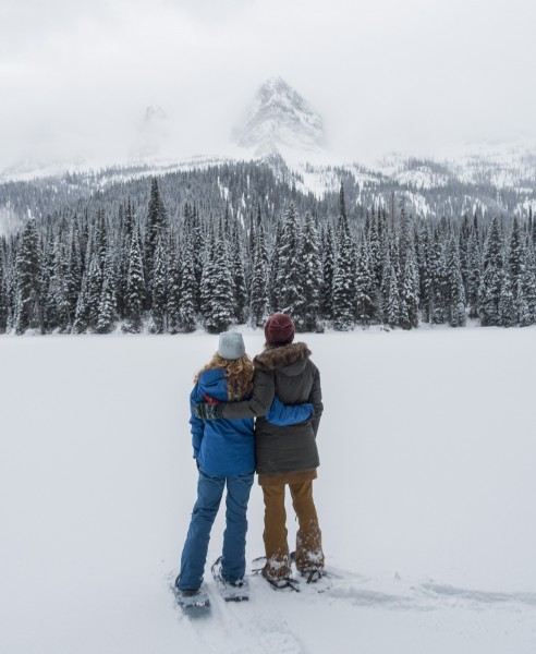 two people hugging on snowshoes looking at scenery, Island Lake Lodge